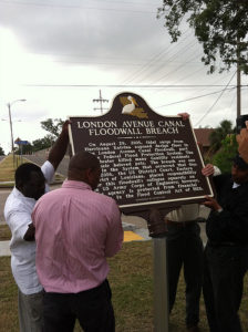 Members of the Gentilly community hoist Historic Plaque onto post near site of London Avenue Canal breach site. Photo/Hubie Vigreux